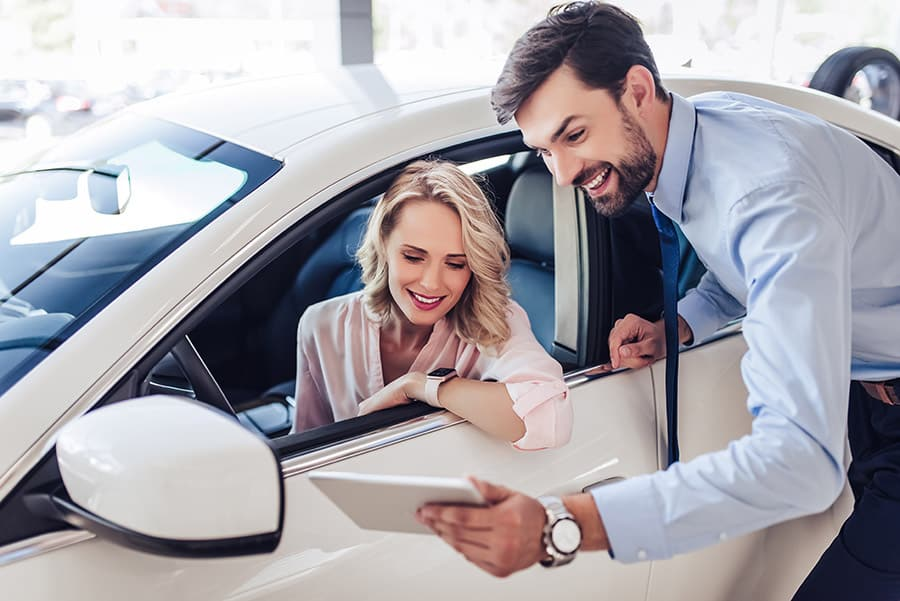 Woman inside car talking to car salesman