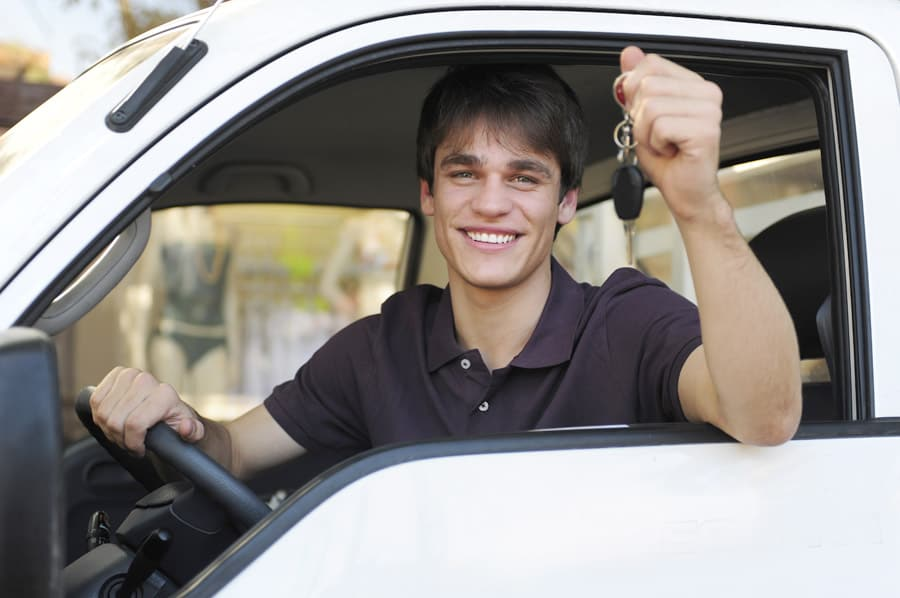 Young man holds up keys to new car