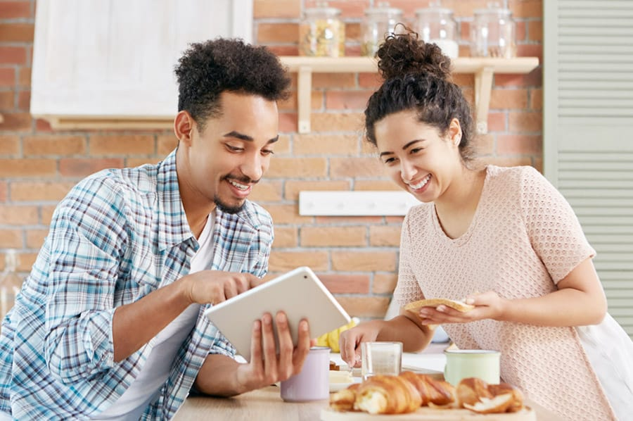 Couple reviewing something online while making lunch
