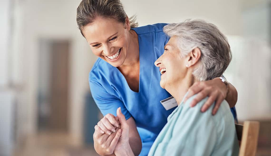 Shot of a young caregiver caring for her elderly patient in her home